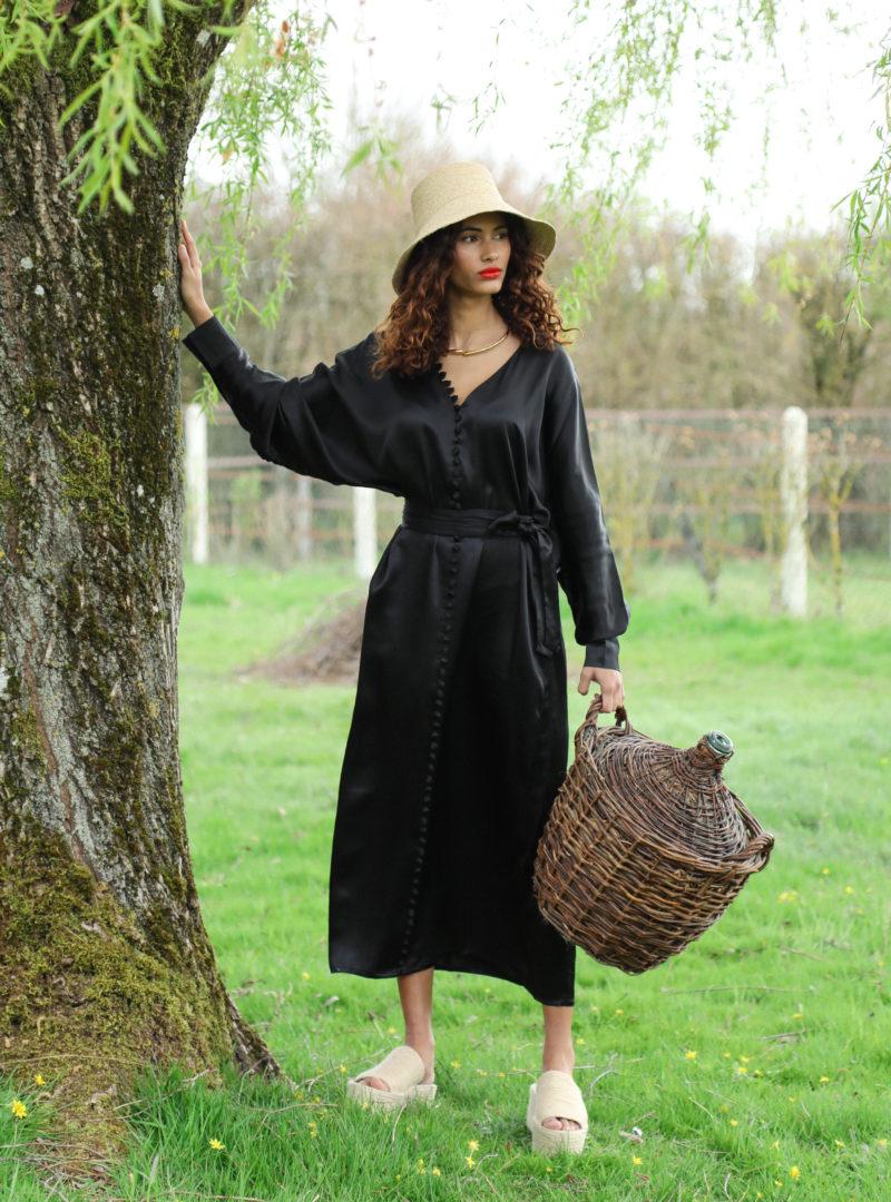 femme tenant un panier portant un chapeau et une longue robe noire à boutons envelope1976 sanna conscious concept