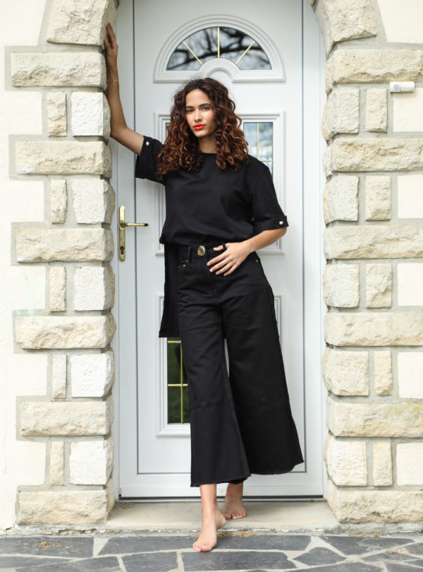 woman wearing a black t-shirt and black pants mother of pearl sanna conscious concept