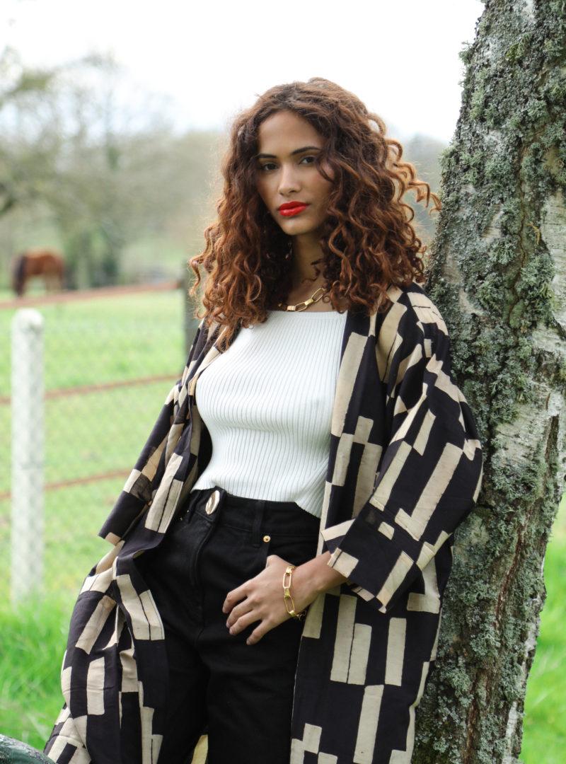 femme portant un kimono beige et noir avec un débardeur blanc et un jean noir the summer house sanna conscious concept