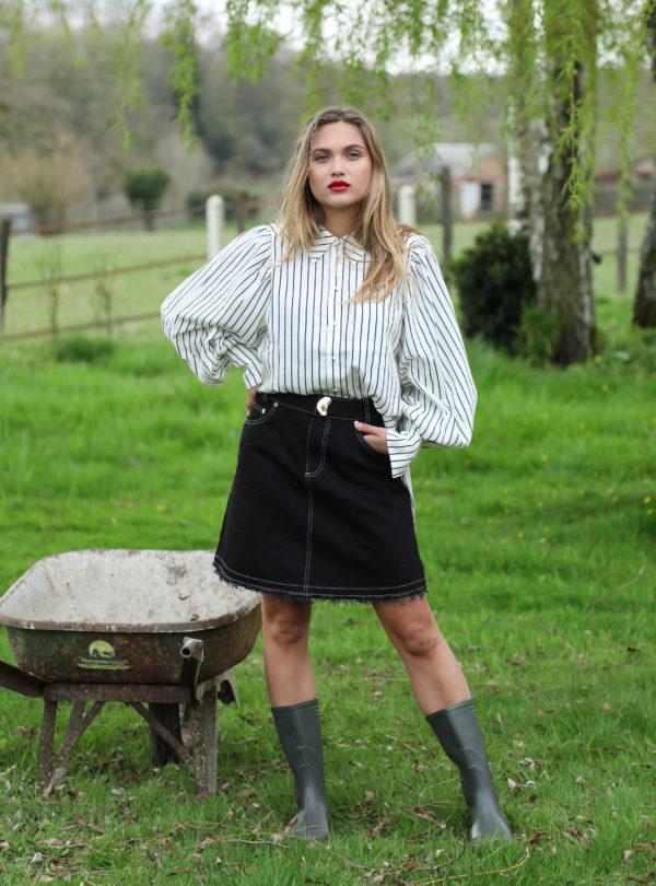 femme portant une chemise à rayures, une jupe en jean et des bottes de pluie mother of pearl sanna conscious concept