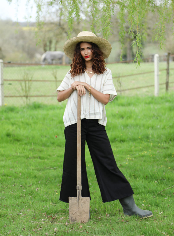 woman holding a shovel and wearing a striped shirt, black jeans and rain boots the summer house sanna conscious concept