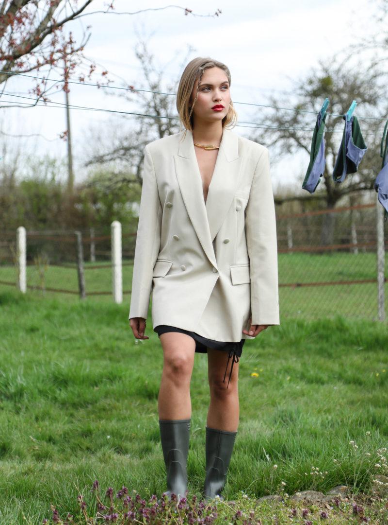femme portant un blazer beige, un jupe noir et des bottes de pluie envelope1976 sanna conscious concept