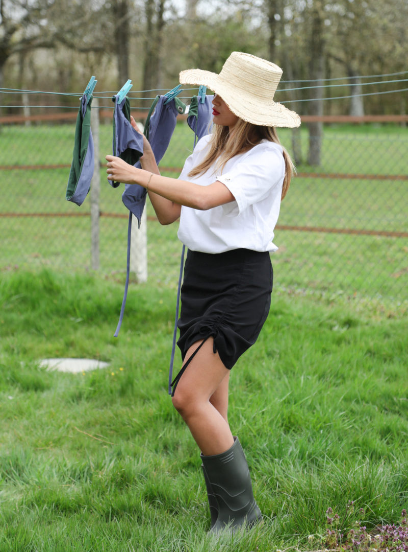 woman wearing a hat, a white t-shirt, a black skirt and rain boots