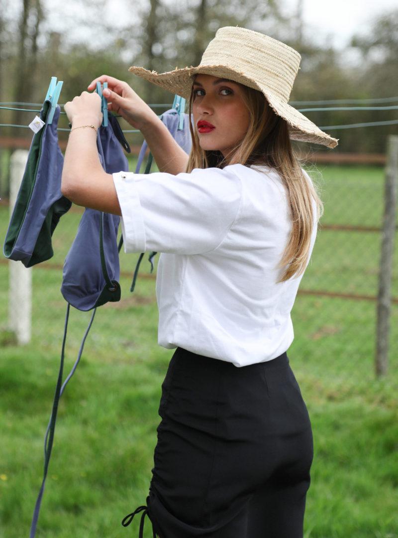 woman wearing a hat, a white t-shirt, a black skirt envelope1976 sanna conscious concept