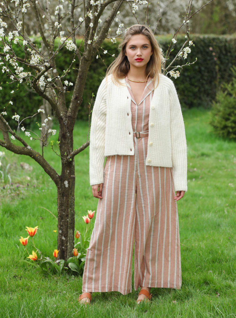 woman wearing a beige cardigan and a brown jumpsuit with white stripes the summer house sanna conscious concept
