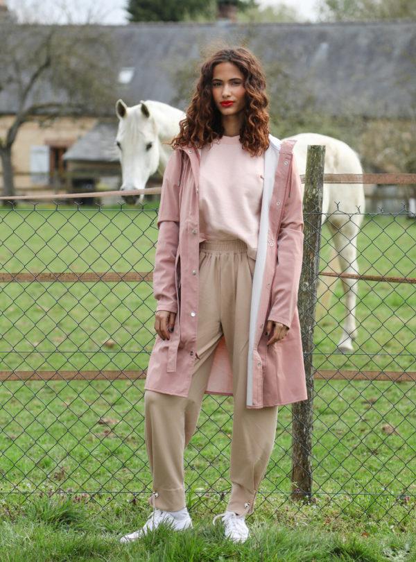 femme portant un sweat rose, un pantalon beige et un veste rose rains sanna conscious concept