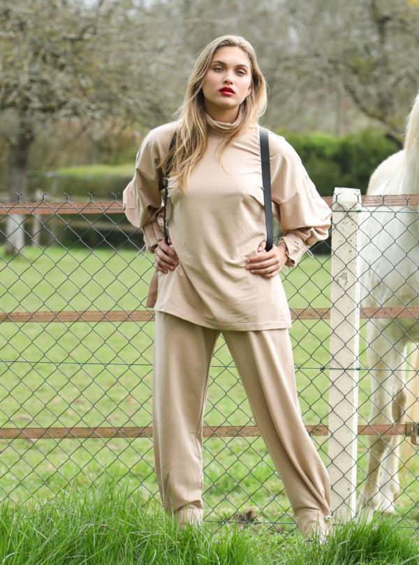 woman wearing a beige turtleneck and beige pants mother of pearl sanna conscious concept