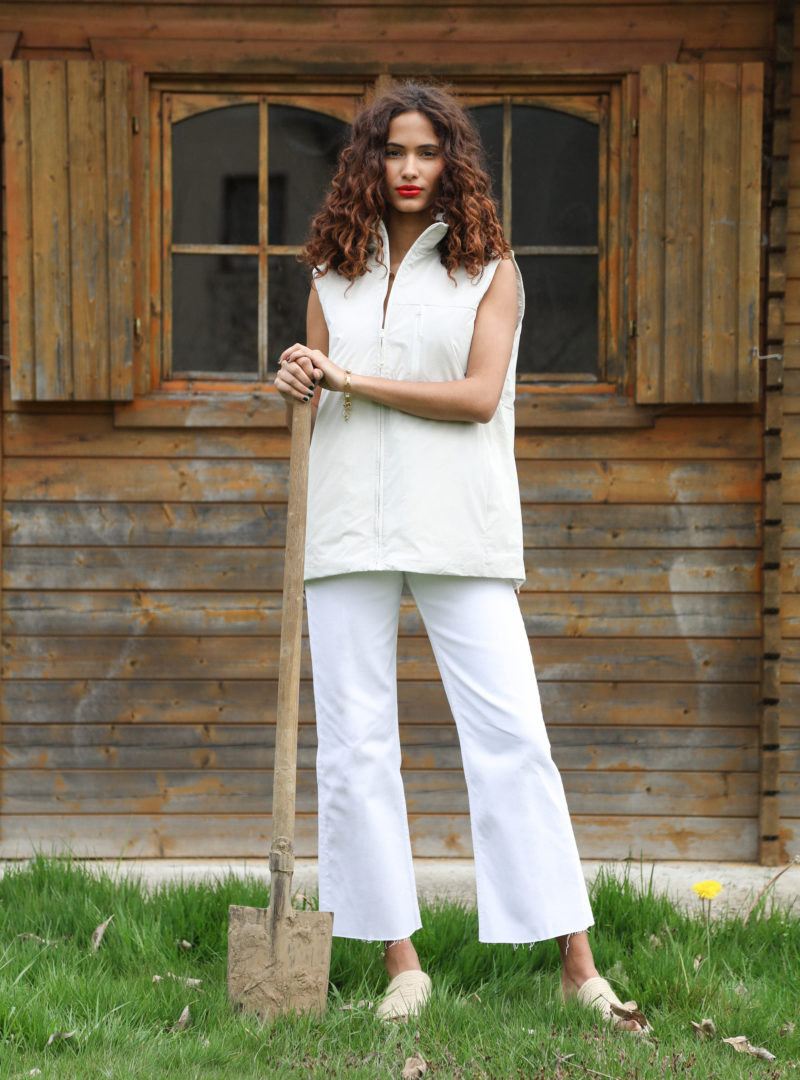 woman holding a shovel and wearing a white sleeveless jacket with a white pants rains sanna conscious concept