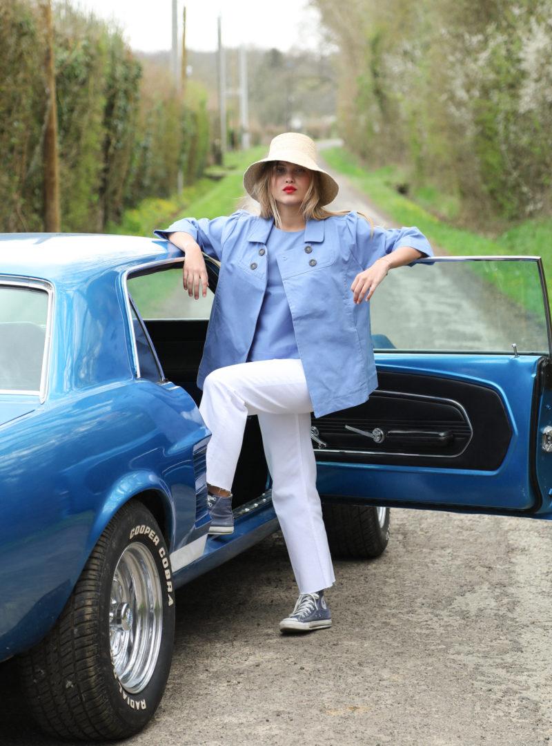 femme portant un chapeau, une veste bleue, un haut bleue et un jean blanc the summer house sanna conscious concept