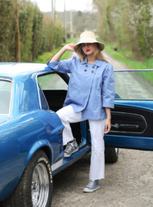 woman wearing a raffia hat from indego africa a blue jacket from the summer house and white jean from boyish jeans sanna conscious concept