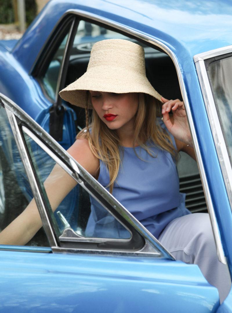 femme portant un chapeau, un haut bleu et un jean blanc indego africa sanna conscious concept