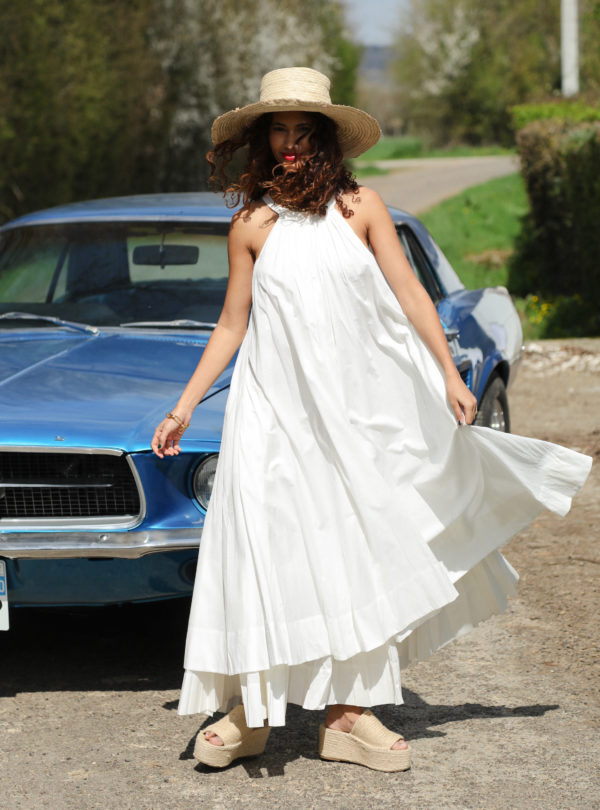 woman wearing a hat and a long white dress the summer house sanna conscious concept