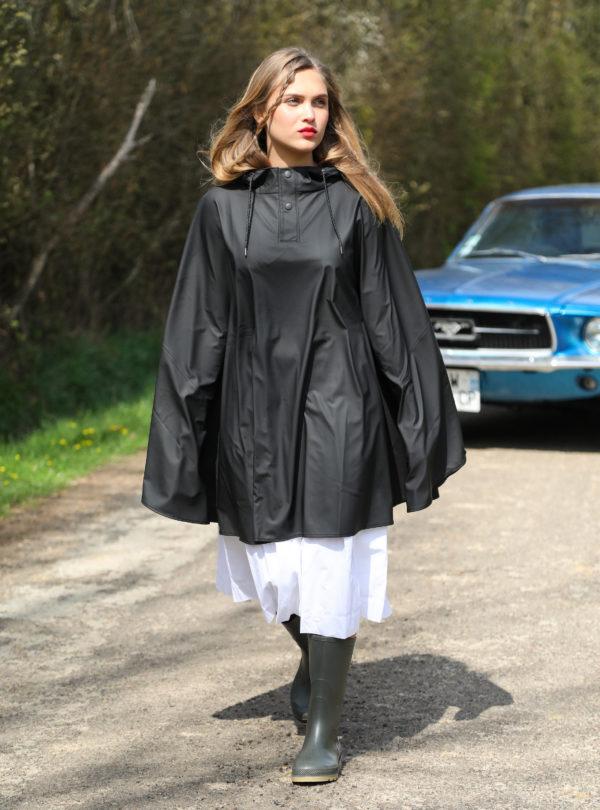 woman wearing a black cape over a white dress and rain boots rains sanna conscious concept