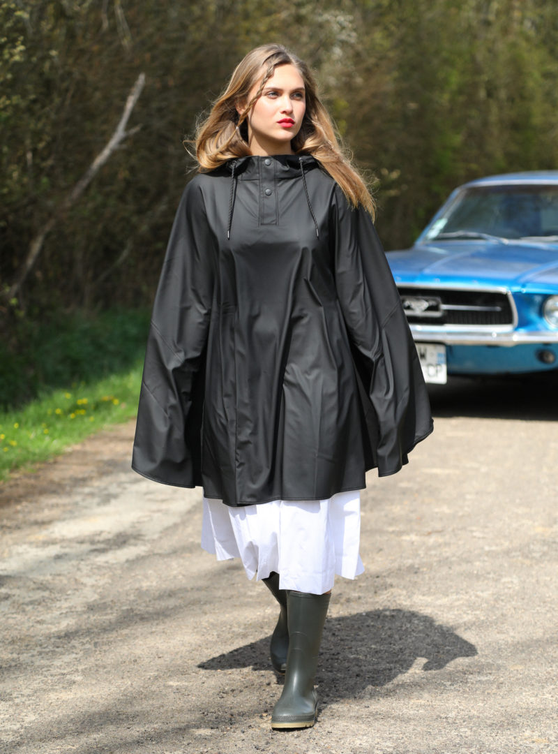 woman wearing a black cape over a white dress and rain boots rains sanna conscious concept