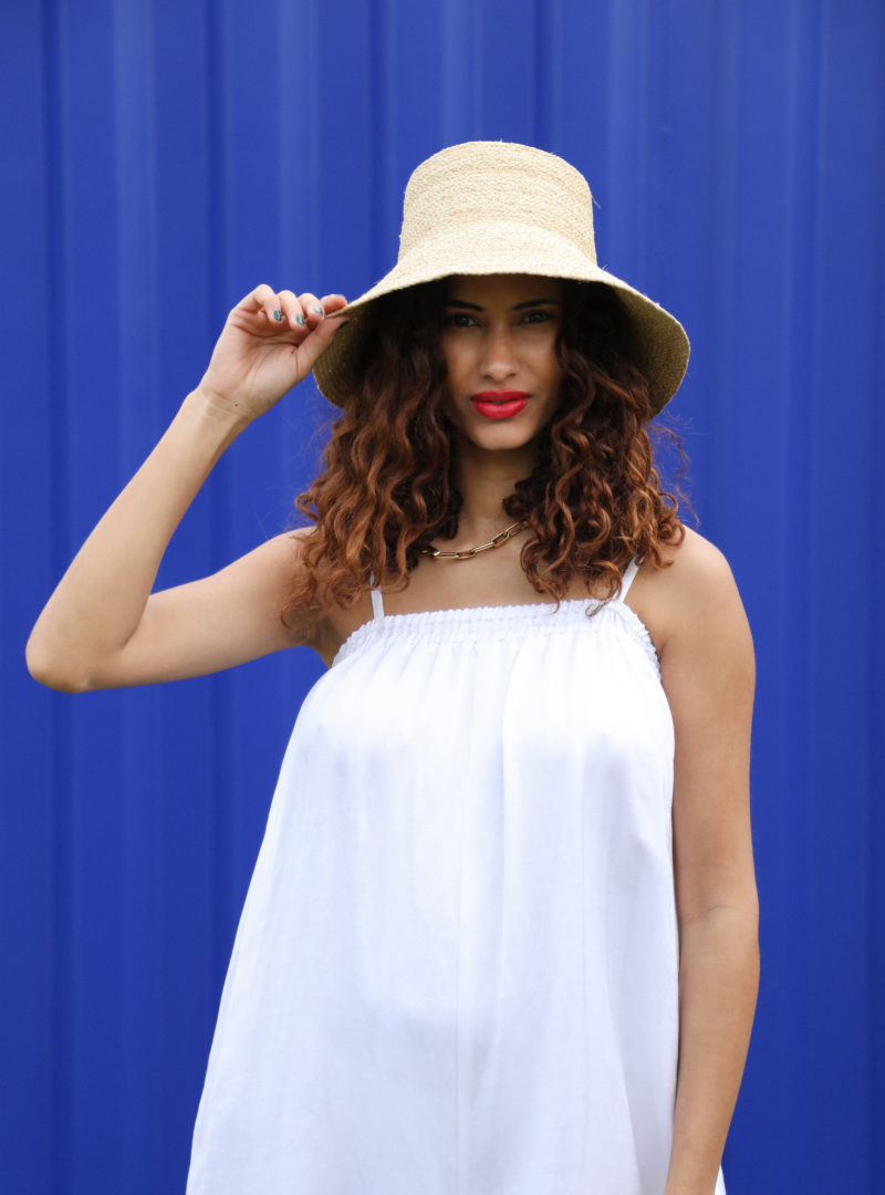 woman wearing a hat with a white jumpsuit ohsevendays sanna conscious concept