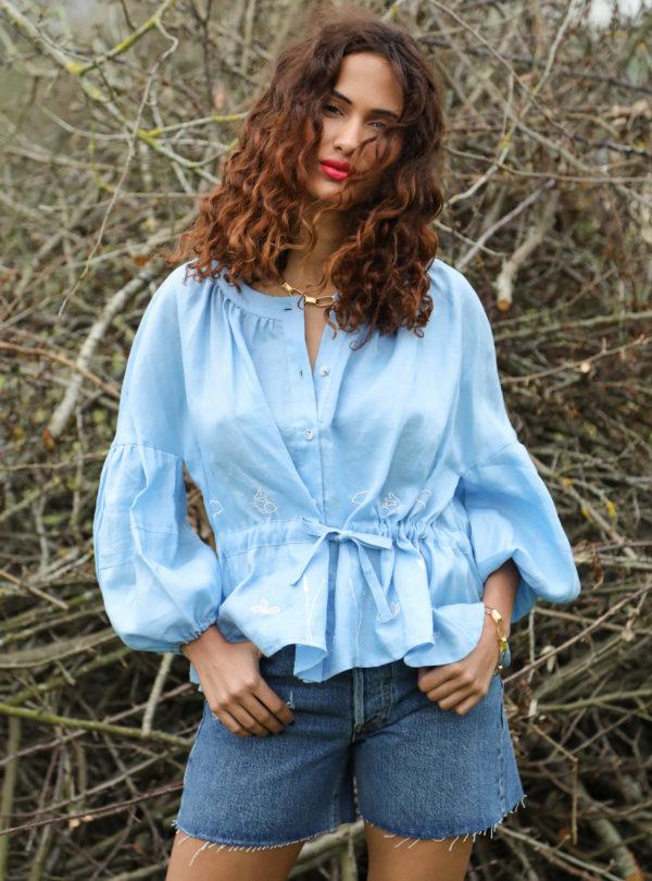 femme portant une blouse bleue, avec un short en jean et des bottes de pluie ohsevendays sanna conscious concept