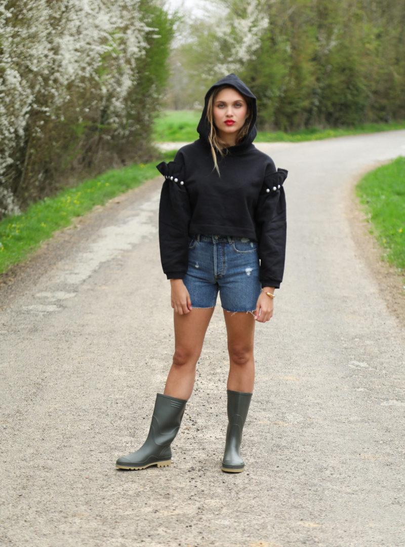 femme portant un sweat noir avec un short en jean et des bottes de pluie mother of pearl sanna conscious concept