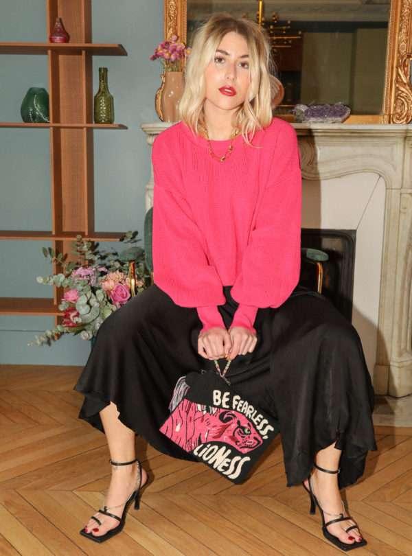 femme portant un pull fuchsia une jupe noir et une pochette noire et rose avec une lionne sur le devant mama tierra sanna conscious concept