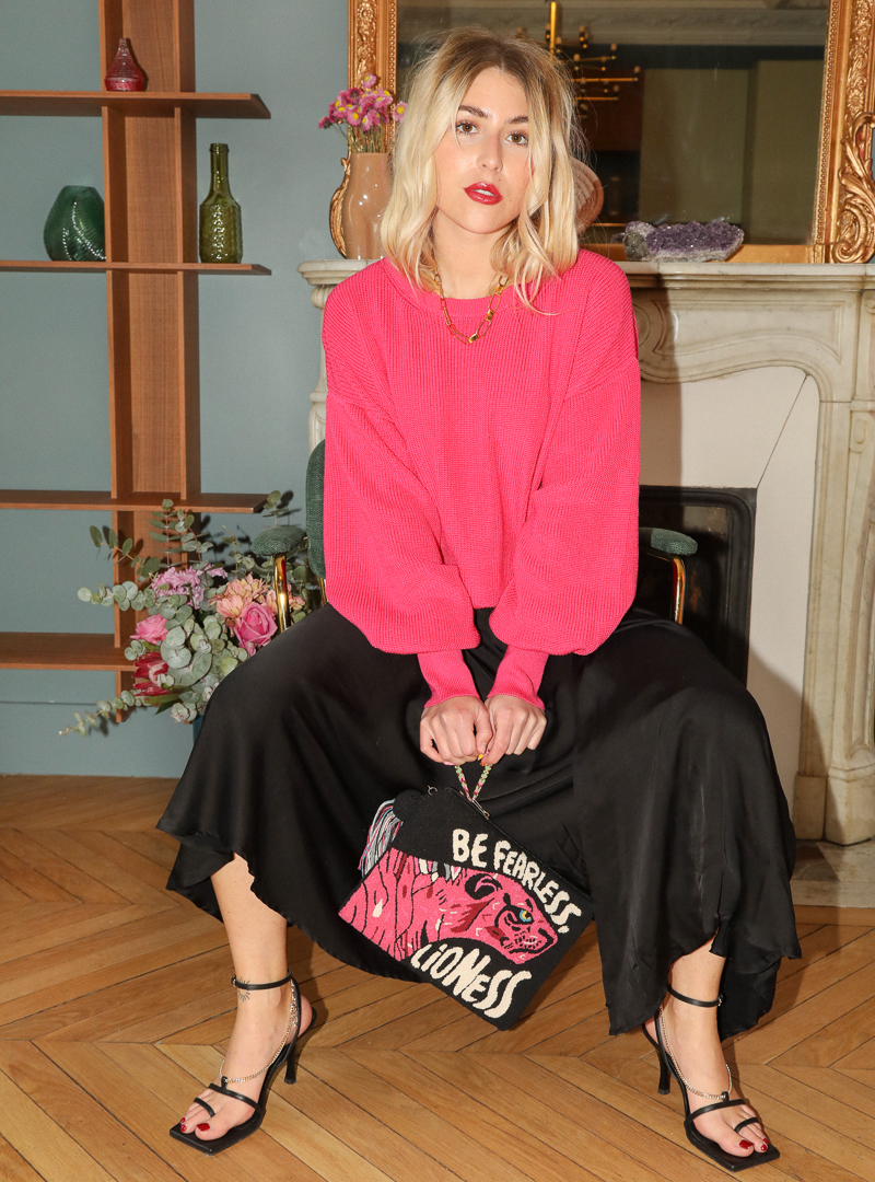 woman wearing a fuchsia sweater a black skirt and a pink and black pouch mama tierra sanna conscious concept