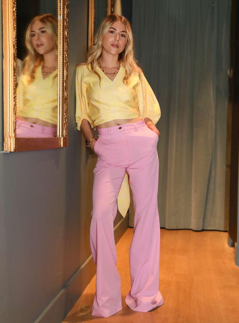 femme portant un cache-coeur jaune et un pantalon évasé rose bogdar sanna conscious concept