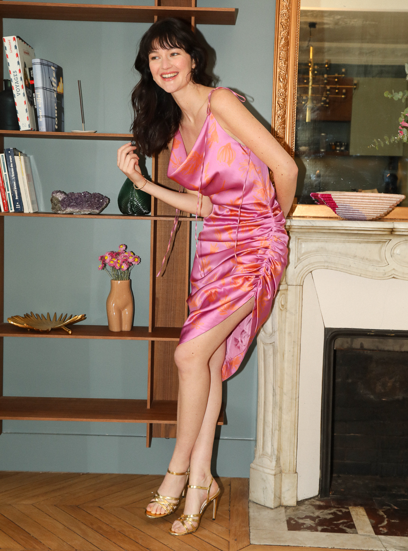 woman smiling wearing a silk ruched dress in pink and orange bogdar sanna conscious concept