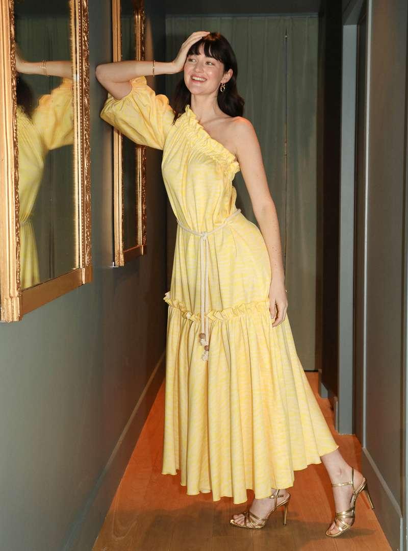 woman wearing a one shoulder maxi yellow dress bogdar sanna conscious concept