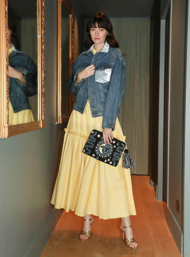 woman wearing a yellow dress and a blue denim jacket holding a blue and black pouch mama tierra sanna conscious concept