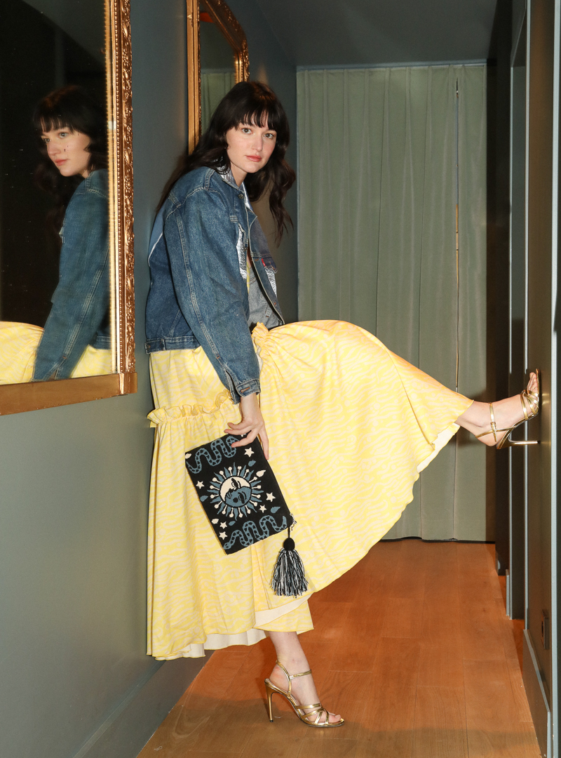 woman wearing a yellow dress and a denim jacket holding a blue and black pouch mama tierra sanna conscious concept