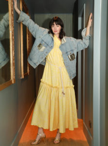 woman wearing the carly dress from bogdar and a denim jacket in gold anotherland sanna conscious concept