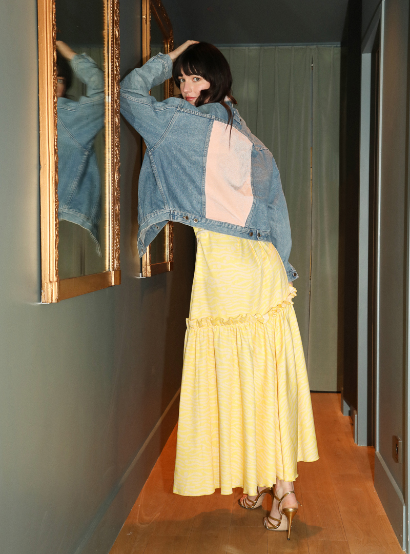 woman wearing the pink denim jacket from anotherland and the carly dress from bogdar anotherland sanna conscious concept