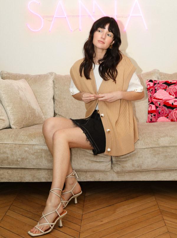 femme assise sur un canapé avec un coussin rose derriere elle mama tierra sanna conscious concept