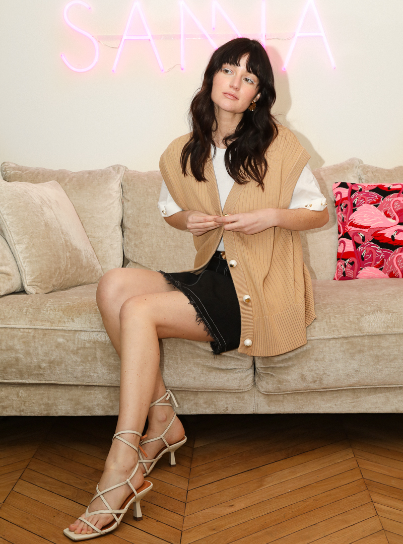 woman siting on a couch with a pink cushion behind her mama tierra sanna conscious concept