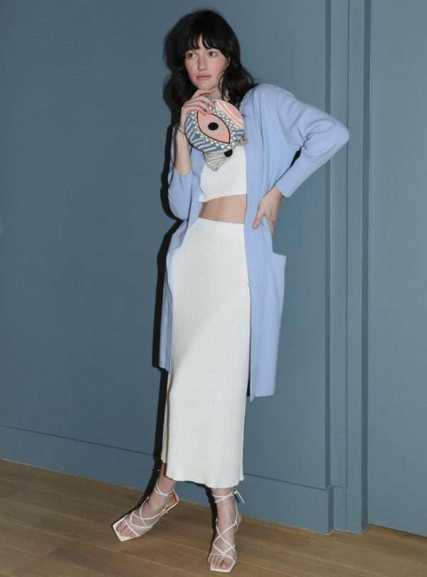 femme portant une pochette un cardigan bleu, un haut blanc et une jupe blanche eleven six sanna conscious concept