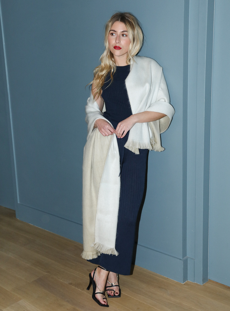 woman wearing a navy pant and a navy top with a beige scarf around her shoulders alpaca loca sanna conscious concept