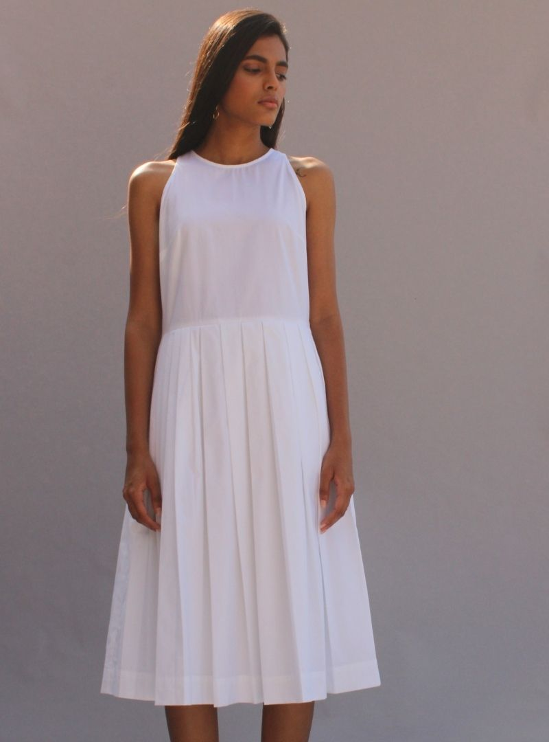 woman wearing a white midi dress stella the summer house sanna conscious concept