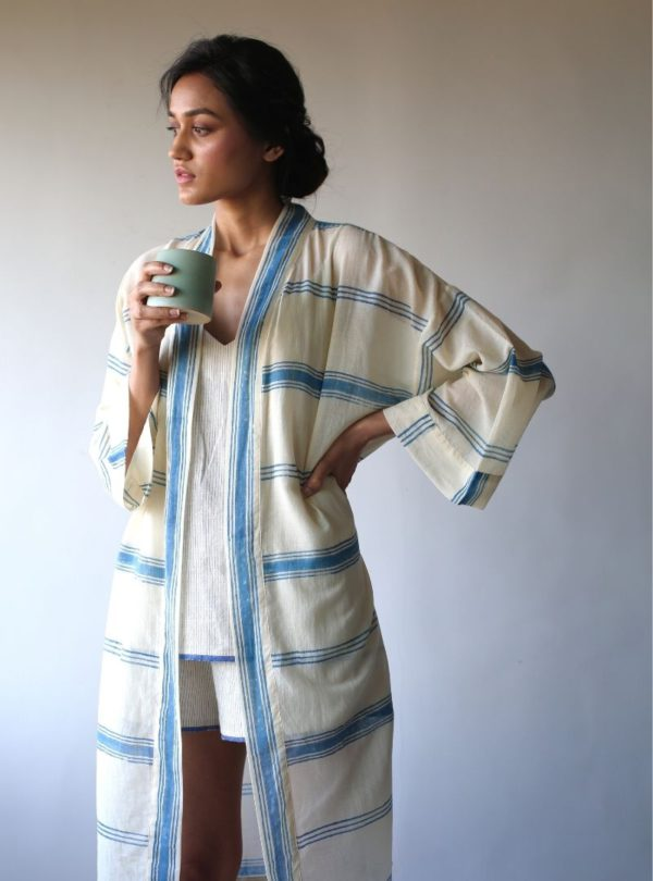 woman holding a cup and wearing a blue and white kimono the summer house sanna conscious concept