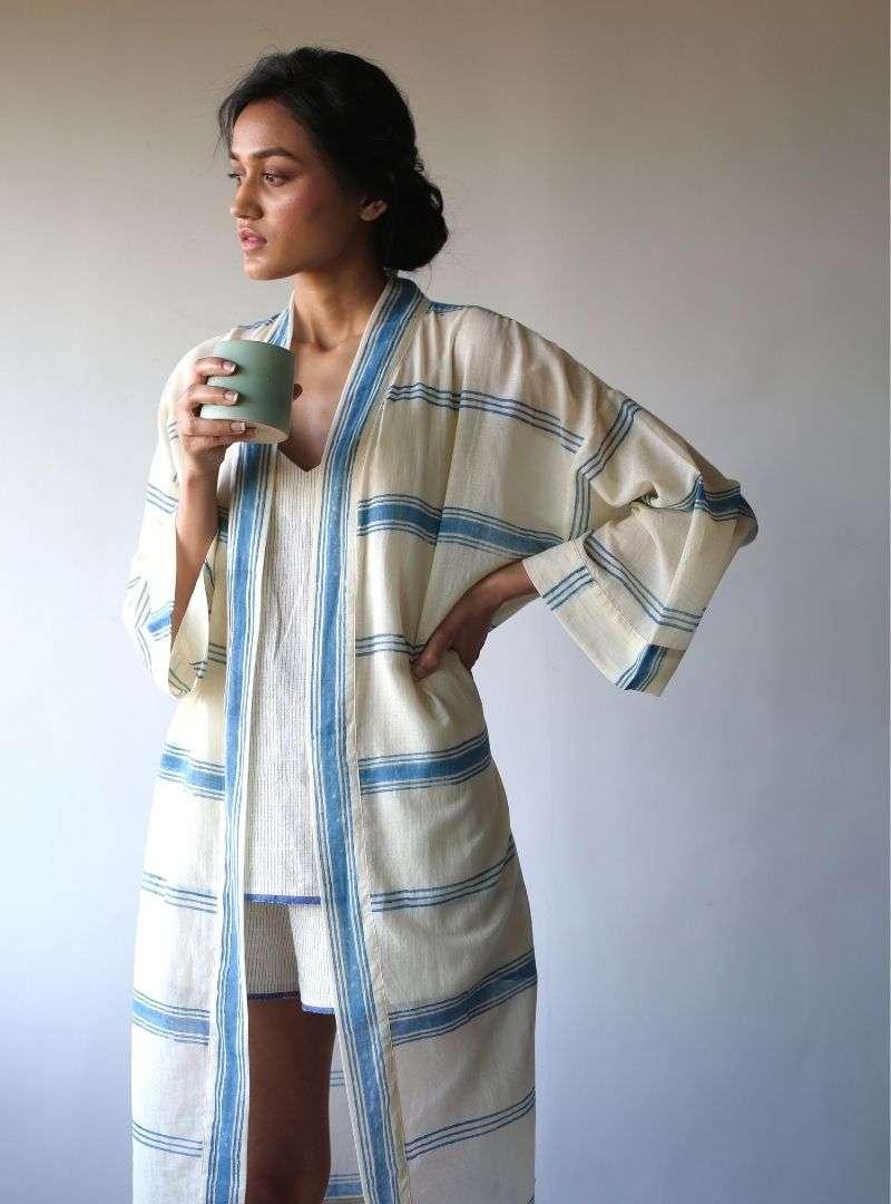 femme tenant une tasse à la main et portant portant un kimono bleu et blanc the summer house sanna conscious concept