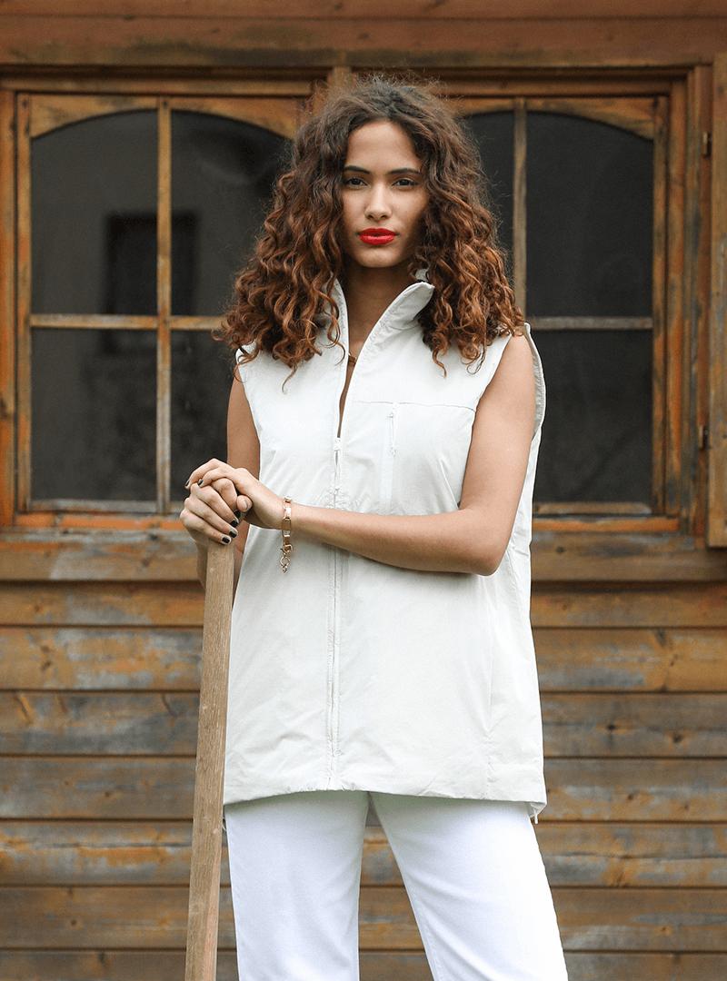 femme tenant une pelle et portant une doudoune blanche sans manches avec un pantalon blanc rains sanna conscious concept