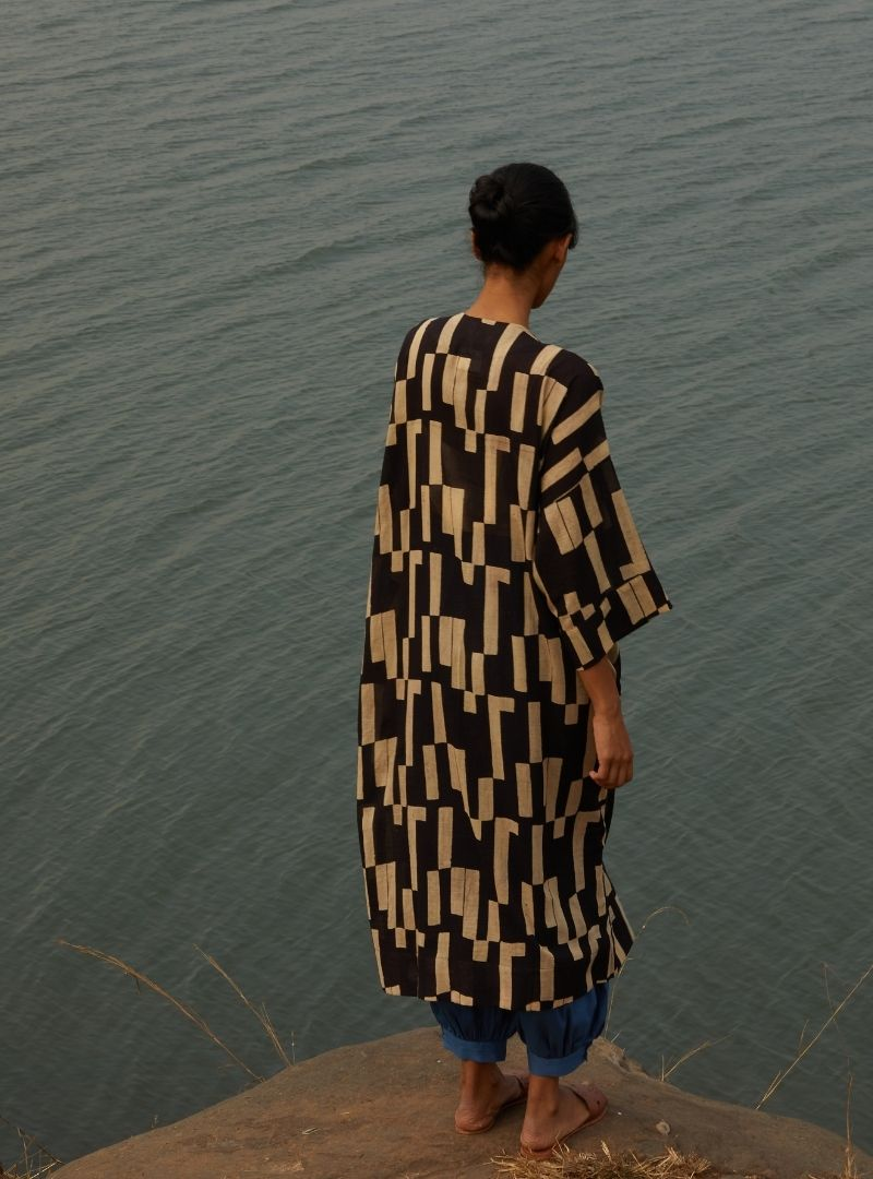 woman in front the sea wearing a black and beige kimono the summer house sanna conscious concept