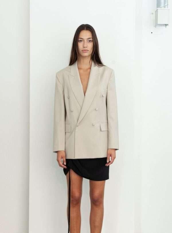 femme portant un blazer beige et une jupe noire envelope1976 sanna conscious concept
