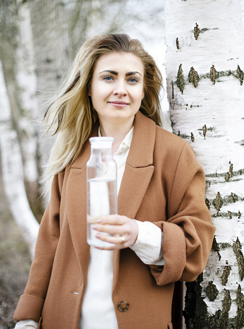 Woman Wearing a White Shirt and Camel Coat Holding a Water Bottle Madara Sanna Conscious Concept