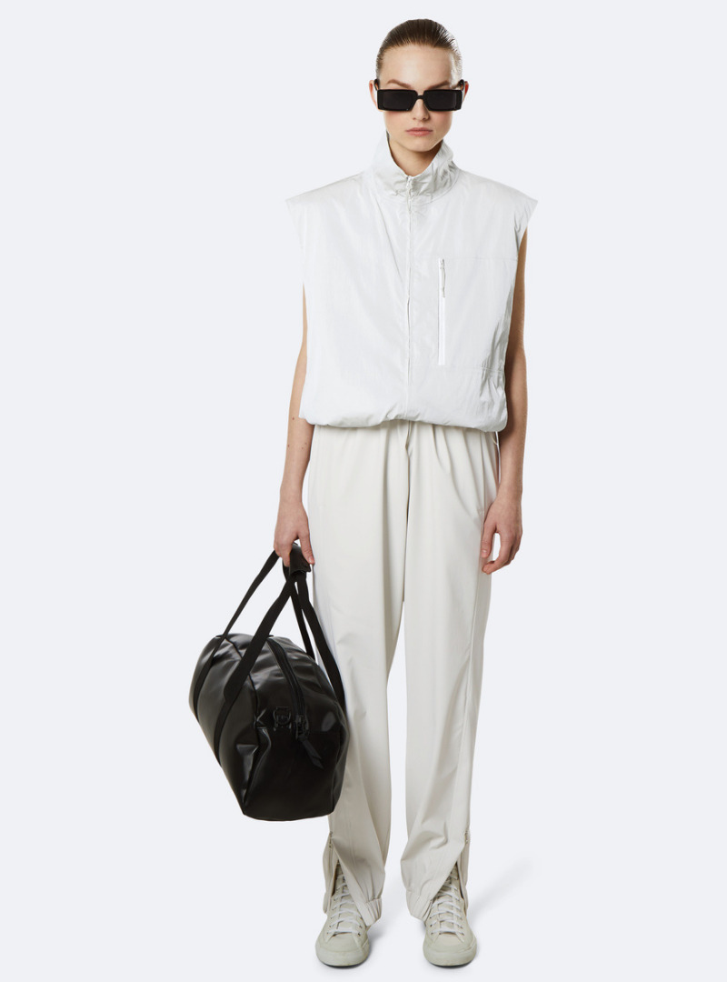 Woman All in White with Black Sunglasses and Holding a Black Bag Rains Sanna Consious Concept