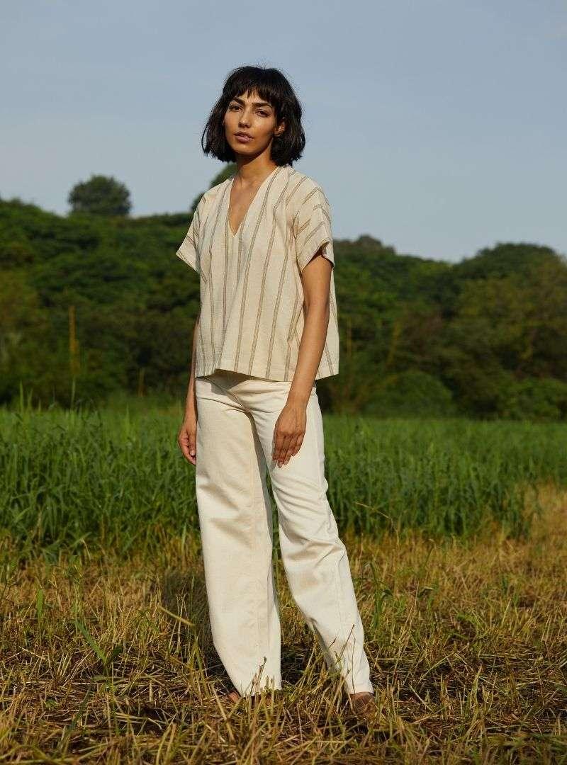 femme portant une chemise rayé en beige et un pantalon beige the summer house sanna conscious concept