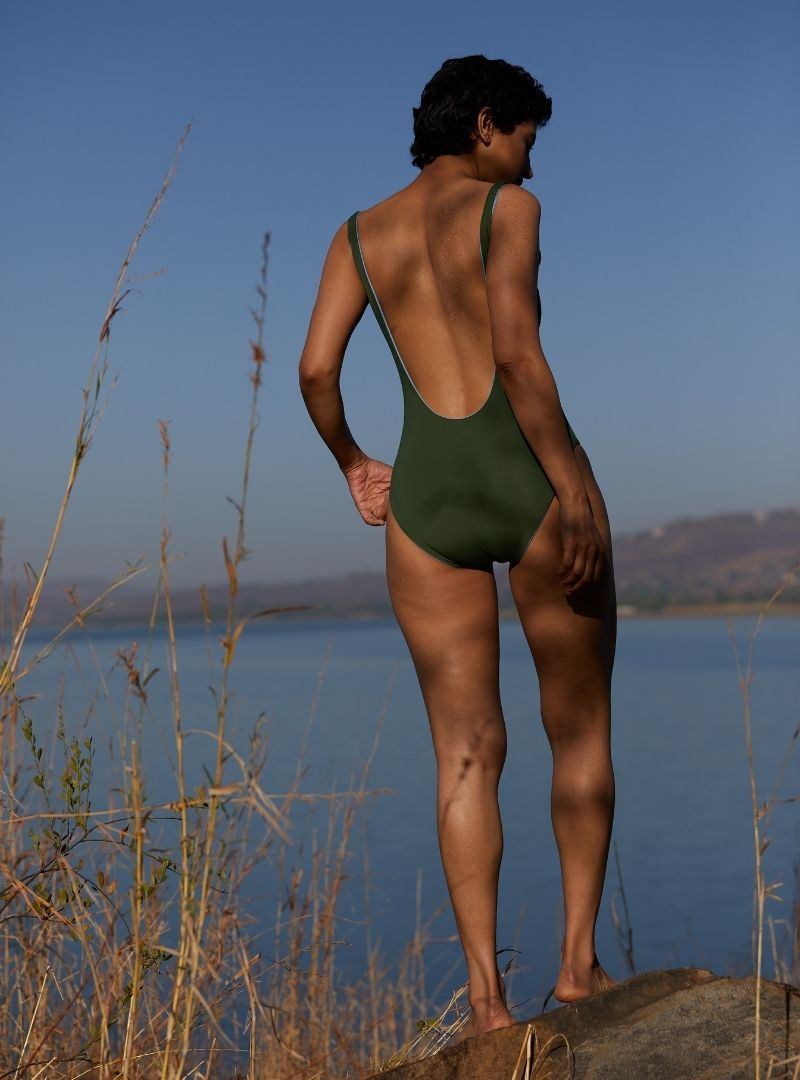 woman wearing a green one piece with an open back the summer house sanna conscious concept