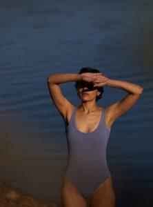 femme se protégeant du soleil avec ses mains et portant un maillot de bain reversible ada lavande the summer house sanna conscious concept