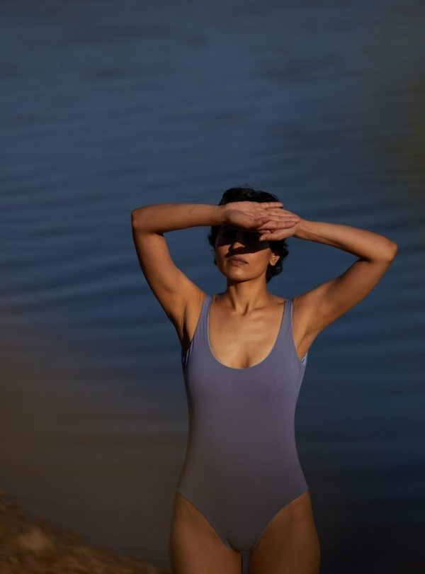 woman protecting herself from the sun with her hands wearing a lavender one piece the summer house sanna conscious concept