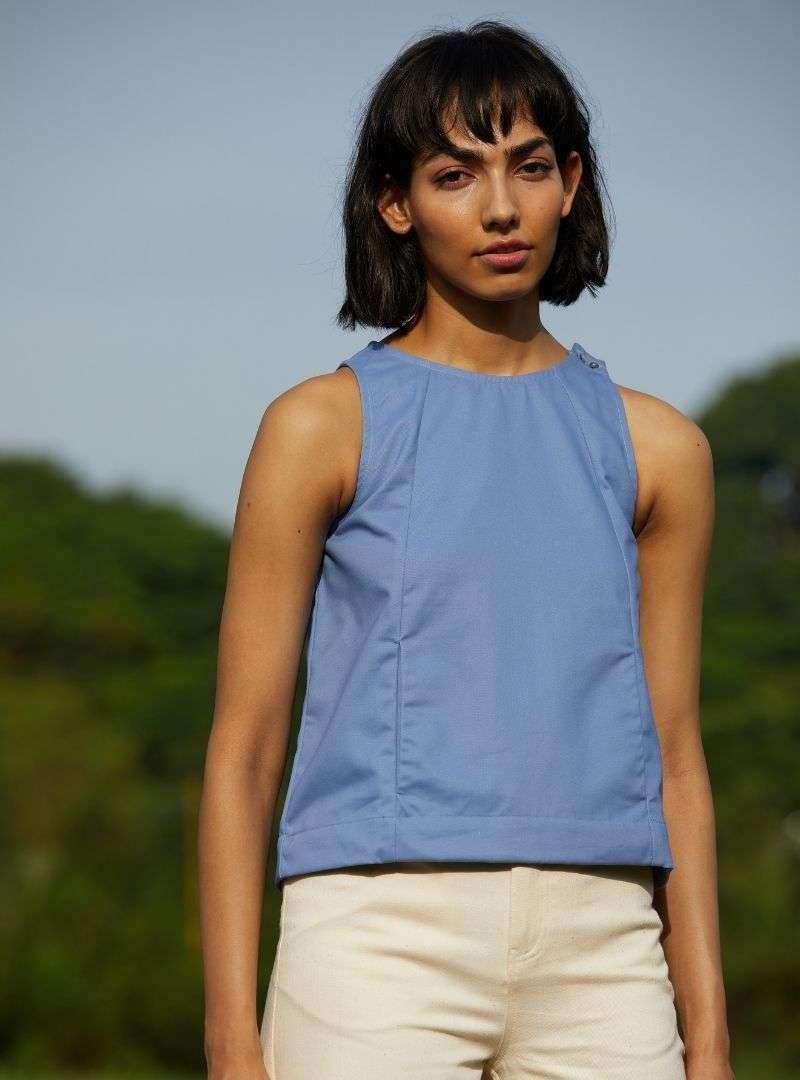 femme portant une débardeur bleu et un pantalon beige the summer house sanna conscious concept