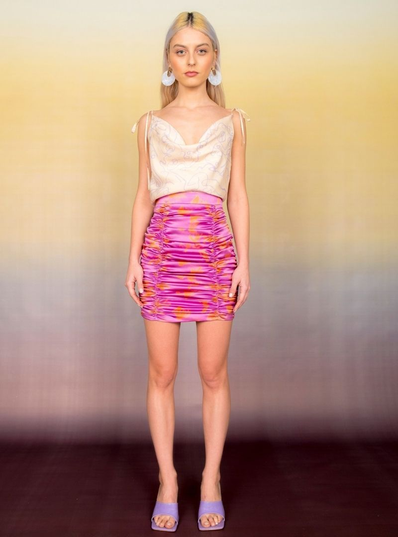 woman wearing a white top and a pink and orange ruched silk skirt bogdar sanna conscious concept