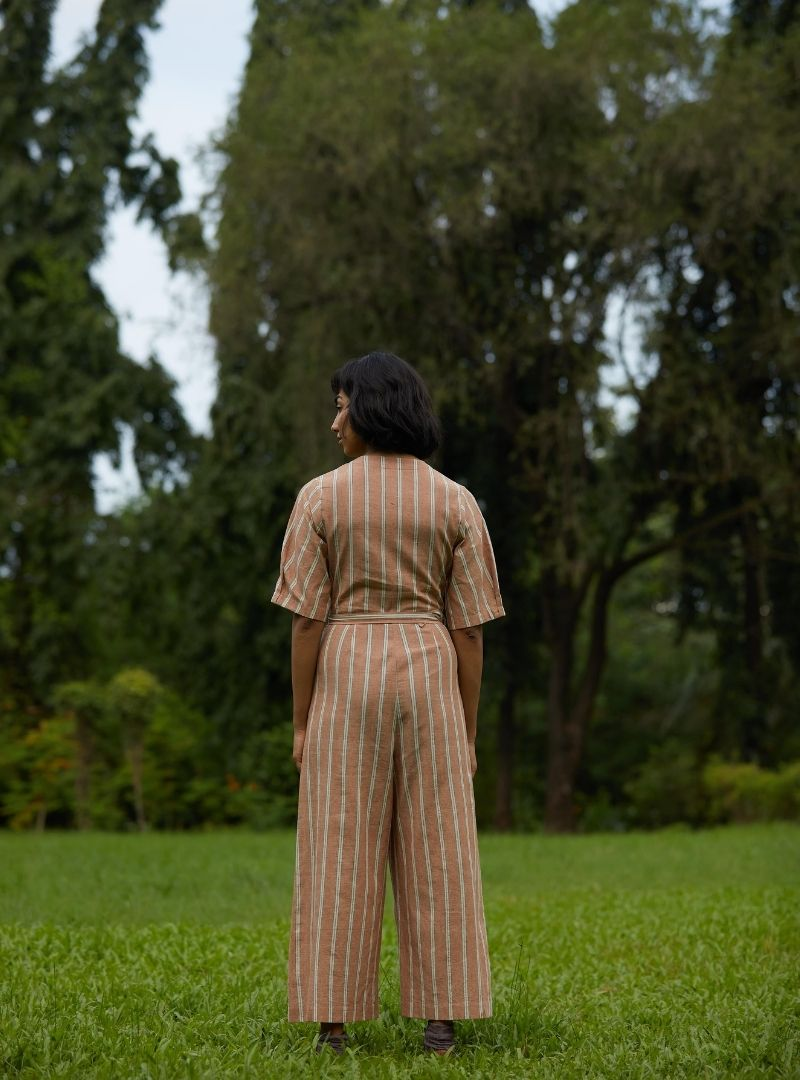 woman wearing a brown jumpsuit with white stripes the summer house sanna conscious concept