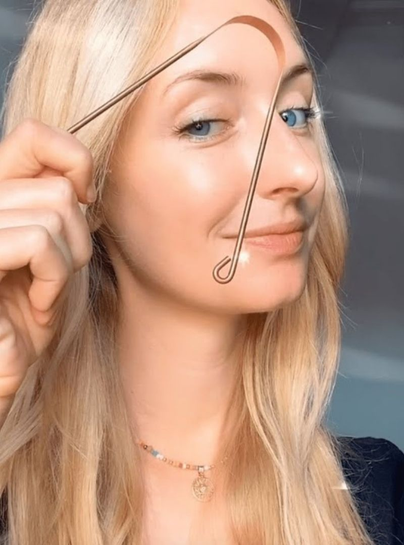 woman holding a copper tongue scraper COSMIC DEALER sanna conscious concept